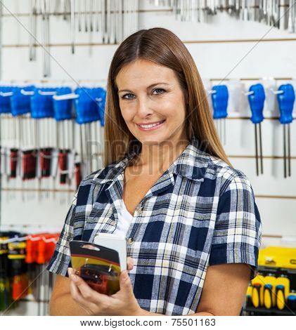 Portrait of female customer scanning product's barcode through cellphone in hardware store