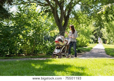 Full length of young mother pushing baby carriage in park