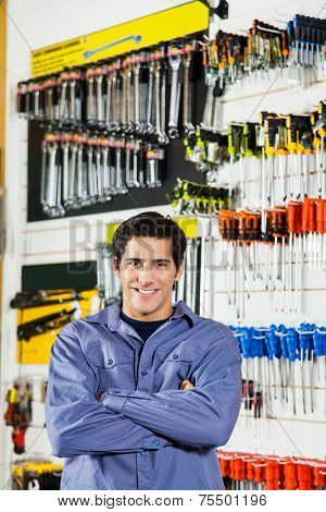Portrait of confident male customer standing arms crossed in hardware shop