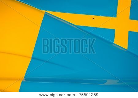 The colors and crest of the national flag of Sweden painted on the body work of a race car