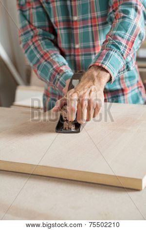 Midsection of male carpenter using planer on wooden plank in workshop