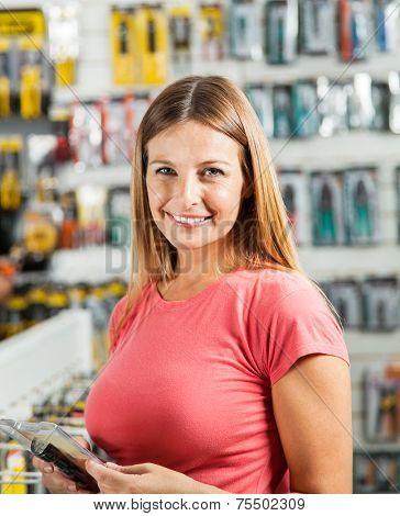 Portrait of happy mid adult woman buying tools in hardware store