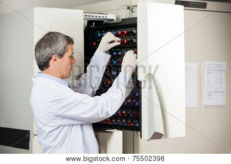 Side view of male technician placing bottles into blood culture instrument