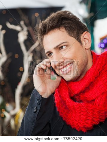 Happy young man using mobilephone in Christmas store