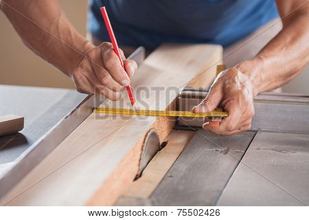 Cropped image of senior carpenter measuring wood at tablesaw in workshop