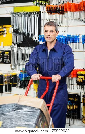 Mature worker in overalls pushing trolley in hardware shop