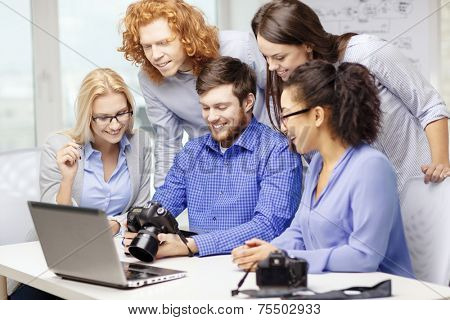 business, office and startup concept - smiling creative team with laptop computer and photocameras working in office