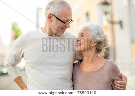 family, age, tourism, travel and people concept - senior couple hugging on city street