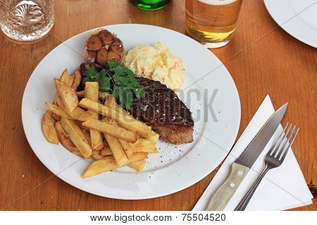 Piece of steak with french fries, coleslaw and fried garlic.