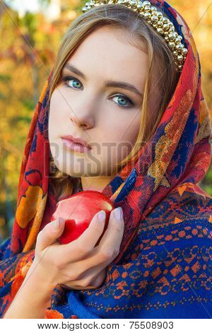 beautiful young sweet girl in a headscarf with the rim on the head with a red Apple in his hand