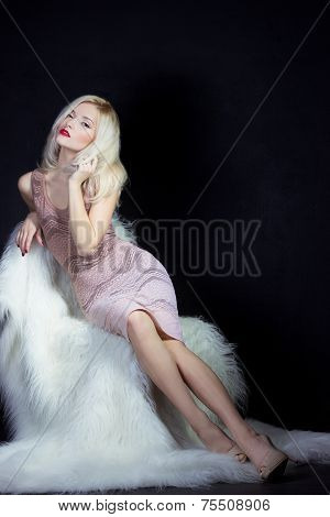 beautiful sexy elegant eye-catching the blonde girl with bright makeup in pink dress in the Studio