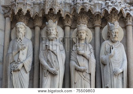 Paris - West facade of Notre Dame Cathedral. Saints statues on The Saint Anne portal and tympanum