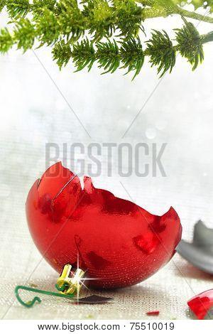 Broken red Christmas ornament under tree branch