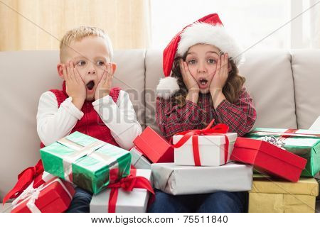Festive siblings surrounded by gifts at home in the living room