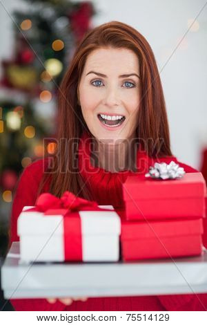 Festive redhead holding pile of gifts at home in the living room