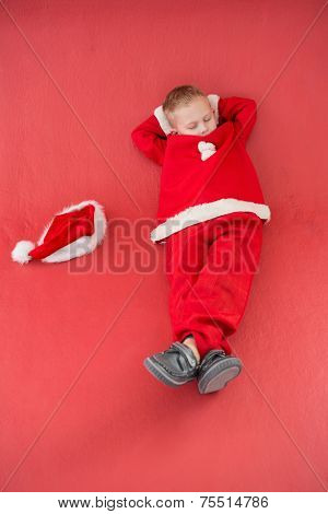 Little boy napping in santa costume on red background