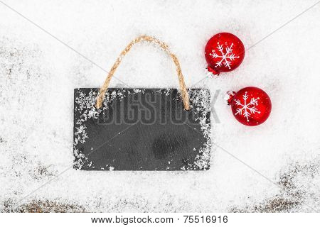 Black Board Of Slate On Rustic Wooden Background With Snow
