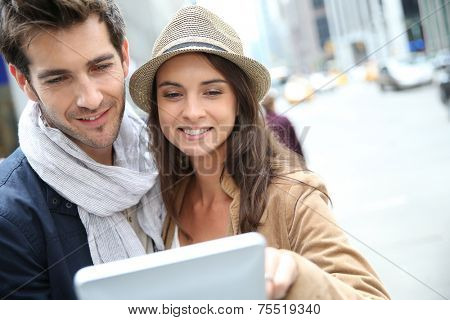 Couple looking at New York city tourist information on tablet