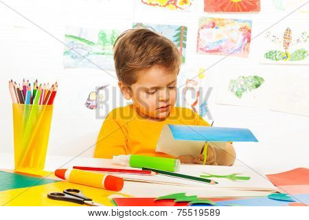 Cute small boy crafting and sitting at the table