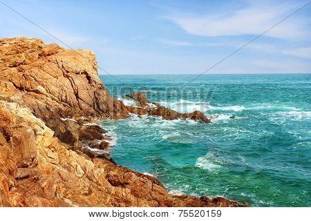 Rocky craggy ocean coastline with turbulent water in Zipolite, Oaxaca