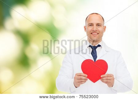 medicine, profession, charity and healthcare concept - smiling male doctor with red heart over natural background