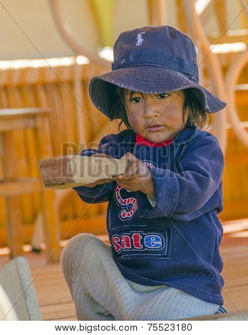 PUNO, PERU, MAY 5, 2014: Uros islands on Titicaca lake -  small boy plays with wood