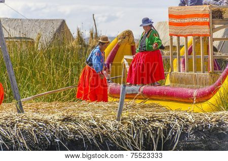 PUNO, PERU, MAY 5, 2014: Uros islands on Titicaca lake -  Local women in traditional attire work on