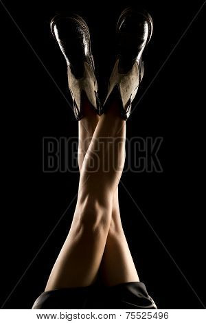 Woman Legs Up On Black Back Lit Boots Legs Crossed
