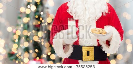 christmas, holidays, food, drink and people concept - close up of santa claus with glass of milk and cookies over tree lights background