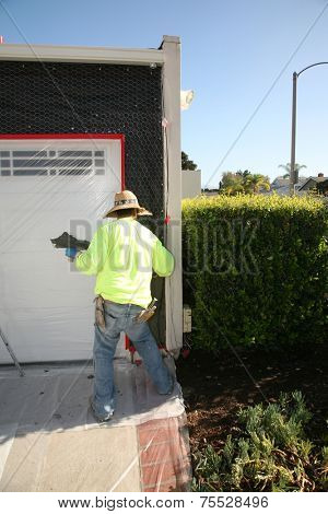 An Unidentifiable contractor applies Stucco to a Home Remodel Project. Stucco is applied to Chicken Wire that is stapled to water resistant paper which is applied to wood so it can be painted