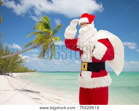 christmas, holidays and people concept - man in costume of santa claus with bag looking far away over tropical beach background