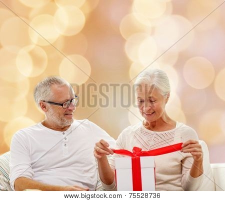 family, holidays, christmas, age and people concept - happy senior couple with gift box over beige lights background