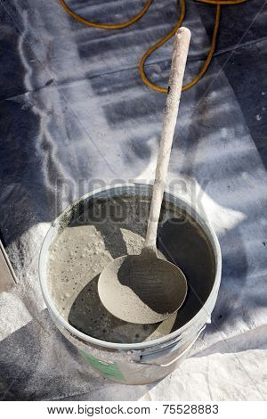 an unidentifiable contractor mixes stucco in a blue plastic drum in preparation of applying it to a home remodel project. stucco is an important part of home remodeling and is very useful