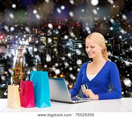 christmas, holidays, technology and shopping concept - smiling woman with shopping bags, credit card and laptop computer over snowy night city background