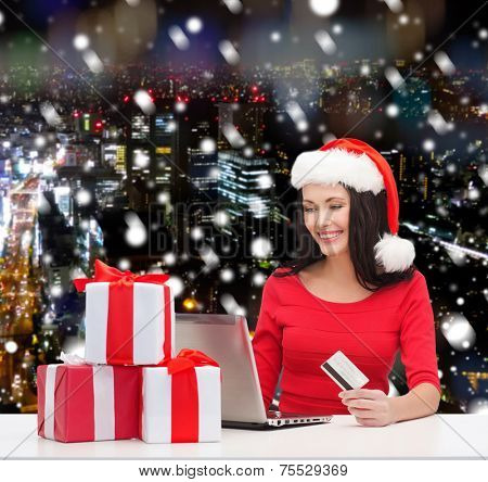 christmas, shopping and people concept - smiling woman in santa helper hat with gift boxes, laptop computer and credit card over snowy night city background