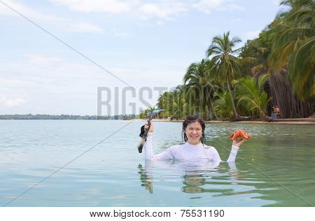 Woman holding the starfish and diving mask