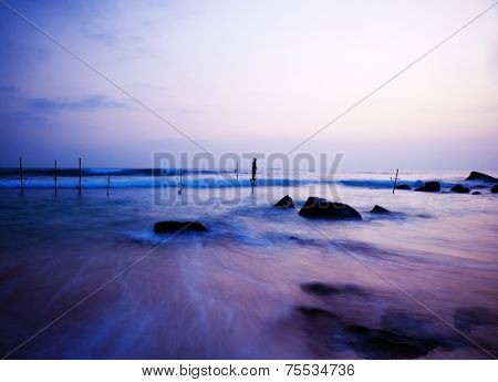 Dreamy Sea coastline, fishing stilts with young boy playing.