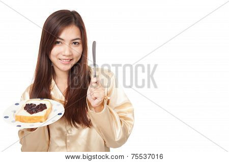 Asian Woman In Pajamas With Bread And Heart Shape Berry Jam
