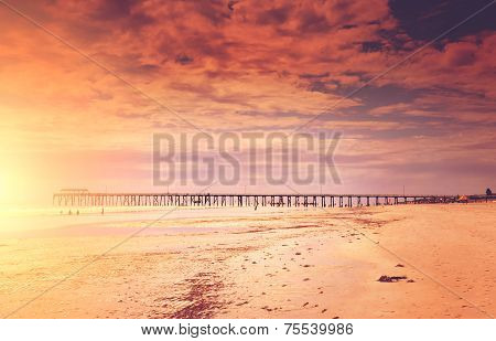 Sunset Style Seascape Overlooking Wide Sandy Beach And Jetty Pier In Background.
