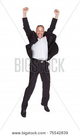 Successful Businessman Jumping With Hands Raised