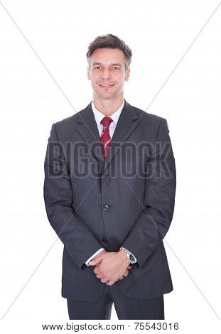 Businessman With Hands Clasped Against White Background
