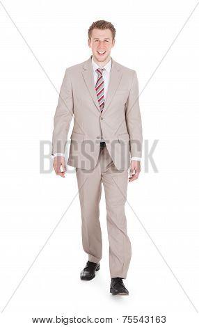 Handsome Businessman Walking Against White Background
