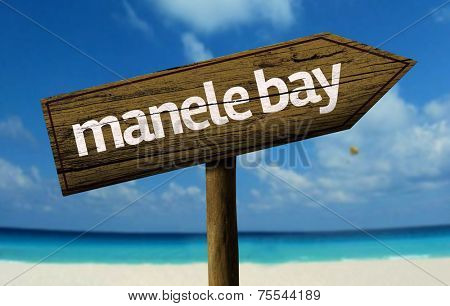 Manele Bay wooden sign with a beach on background