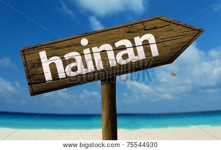 Hainan, China wooden sign with a beach on background