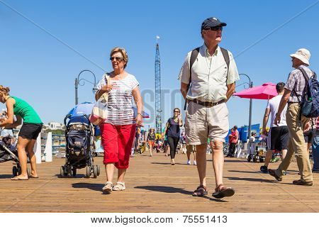 SANTA MONICA, USA - SEP 19: Tourists walk through Santa Monica Pier in Santa Monica, CA on September 19, 2013. The pier is a more than hundred-year-old historic landmark that contains Pacific Park.