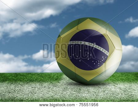 Soccer ball with Brazilian flag in a green field