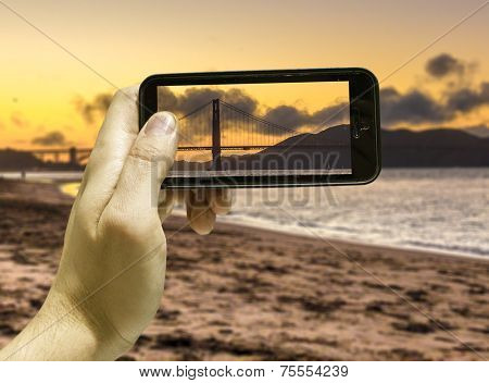 Hand takes a picture of the Golden Gate in San Francisco, USA