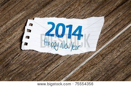 2014, Happy New Year written on the paper on a wood background