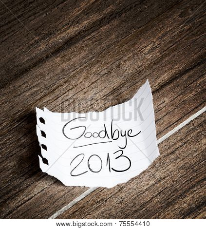 Goodbye 2013 written on the paper on a wood background