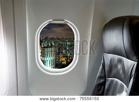 Buildings through aircraft window onto jet engine at night